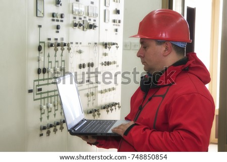 Electrician with laptop reading instruments in power plant control center #748850854