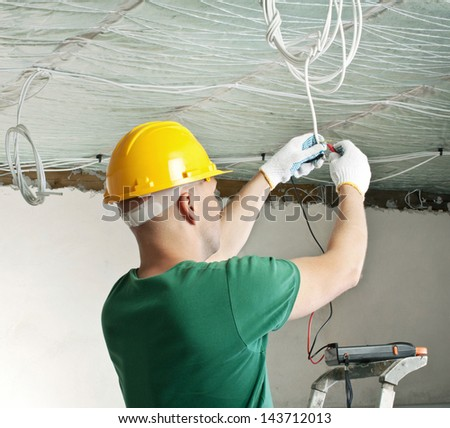 electrician with multimeter checking voltage