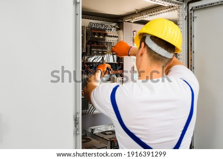 Electrician with screwdriver tighten up switching electric actuator equipment in fuse box. View from the back, a young specialist in a yellow hard hat and overalls. Indoor. Foto stock ©