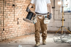 Electrician with tools, working on a construction site. Repair and handyman concept. House and house reconstruction.