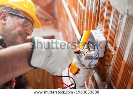 Electrician worker with tester measures the voltage in an electrical circuit breaker; wear helmet, gloves and goggles. Workplace safety.  ストックフォト ©