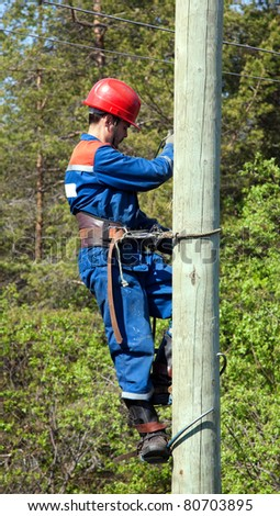 Electrician working at height on a background of green wood
