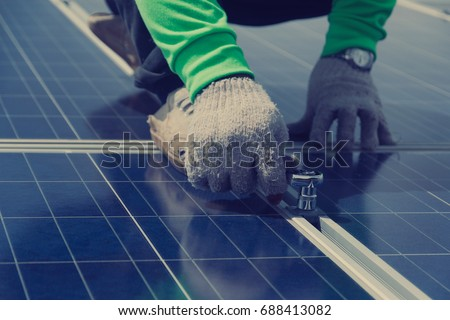electrician working on  maintenance equipment at solar power plant; electrician swapping  solar panel with solar panel voltage drop  #688413082