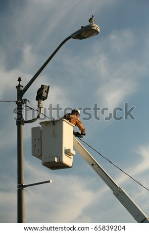 Electrician working on Power line - stock photo