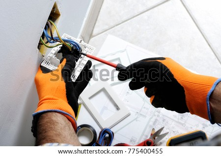 Electrician working safely on switches and sockets of a residential electrical system #775400455