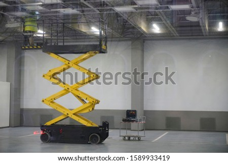 Electrician works stand on electric hoist ( lifting mechanism) and mending ceiling lights. Car parking. night scene.
