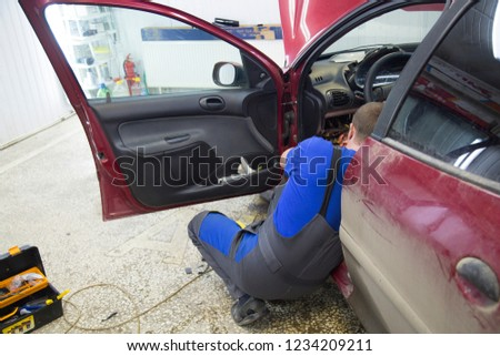 Electrician works with electric block in car. Close-up of automobile inside under raised hood. Service man hands working with cables of auto #1234209211