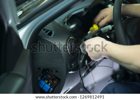 Electrician works with electric block in car. Close-up of automobile inside under raised hood. Service man hands working with cables of auto #1269812491