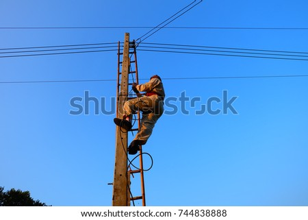 Electricians are climbing electricity poles. To install the electrical system #744838888