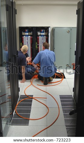 Electricians installing additional power cables in a data center .