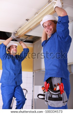 Electricians installing neon on ceiling
