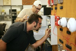 Electricians learning how to wire fire alarm systems in a vocational training class.