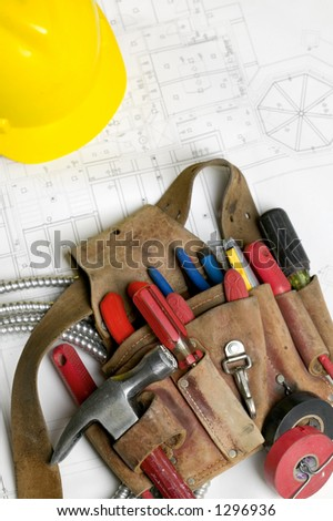 Electricians tool belt, hard hat and electrical plans.
