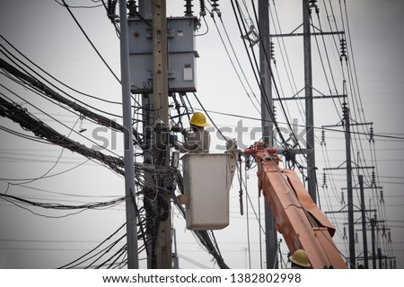 Electricians Wiring Cable repair services.Technician checking fixing broken electric wire on pole.Electricity power utility worker in crane truck bucket fixes high voltage power transmission line.