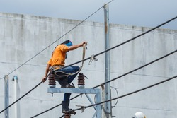 Electricians Wiring Cable repair services,worker in crane truck bucket fixes high voltage power transmission line,setting up the power line wire on electric power pole,Soft focus,selective focus.