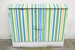 Electricity box painted green, blue and yellow