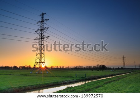 Electricity cable in a typical dutch landscape at sunset
