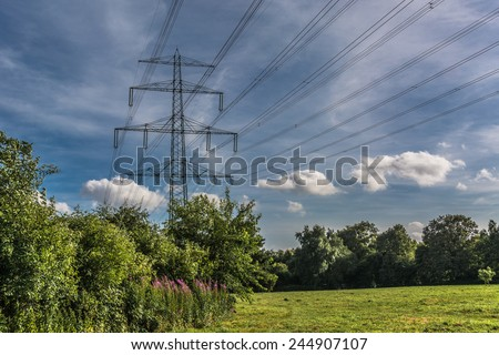 Electricity energy tower in landscape with green trees blue sky \ Electricity energy tower with many cables in landscape with green trees blue sky background