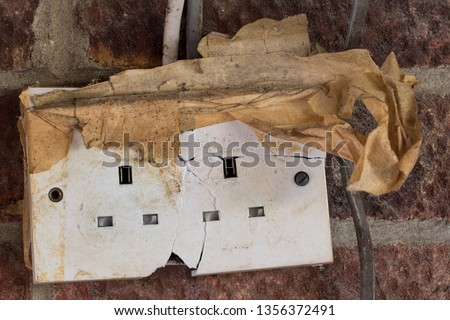 Electricity hazard. Dangerous cracked and damaged electrical power wall socket. Old home garage broken electric plug wiring and cable. Domestic electrics repair job.