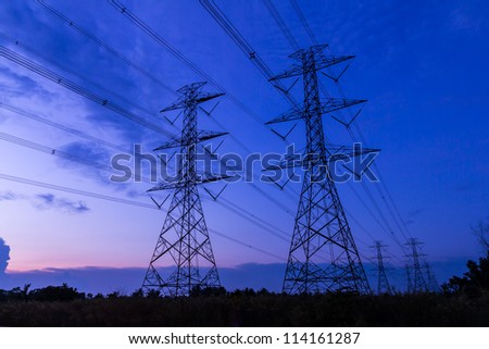 electricity high voltage power post at twilight evening - stock photo