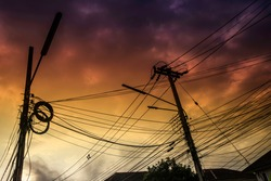 Electricity messy wires on pole. Silhouette at sunset. environment concept