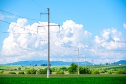 Electricity poles in a row. High voltage poles in the cloudy blue sky. Industrial landscape.