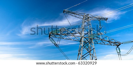 Electricity pylon against blue cloudy sky