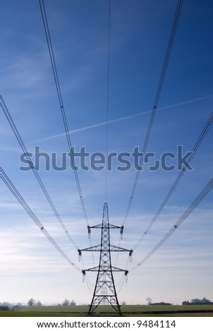 Electricity pylon and cables stretching out into the distance across a green field