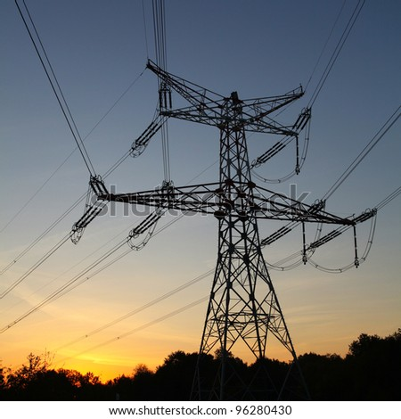 Electricity pylon at orange sunset - stock photo