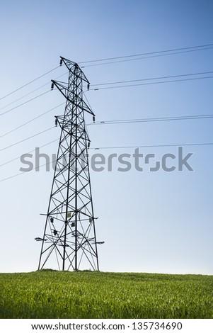 Electricity pylon, blue sky, green field