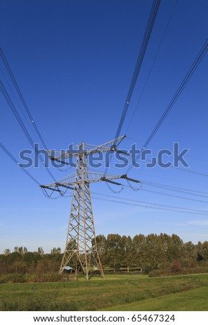 Electricity pylon in perspective against a deep blue sky standing in a green field