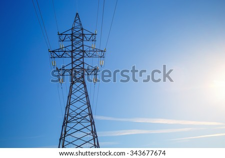 Electricity pylon silhouetted against blue sky background. High voltage tower.