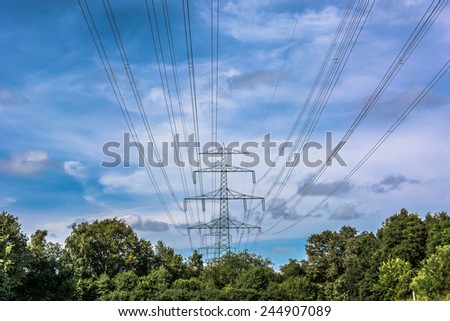 Electricity Pylon tower in landscape with green trees against sky background \ Blue and cloudy sky behind an Electricity Pylon tower in landscape with green trees