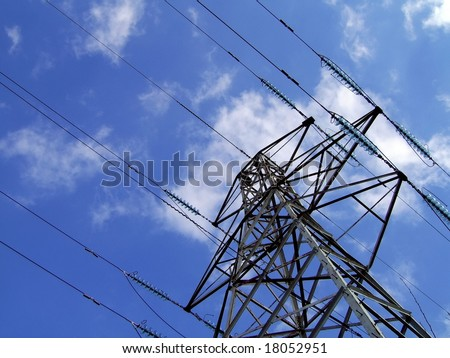 electricity pylon / tower with fluffy white clouds and blue sky background