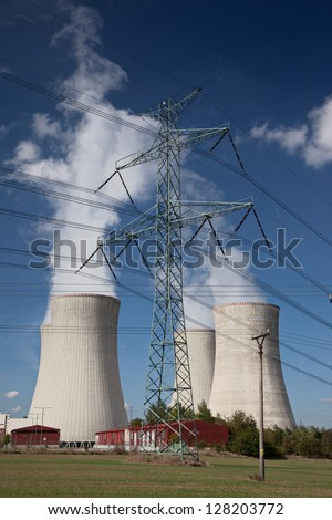 Electricity pylon with power plant cooling tower background