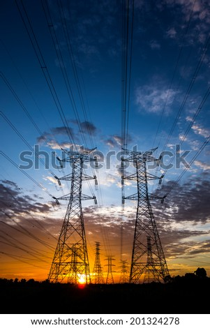 Electricity pylons and cable lines during sunset. Vertical format #201324278