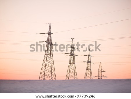 Electricity pylons and lines above a freeway  at sunrise