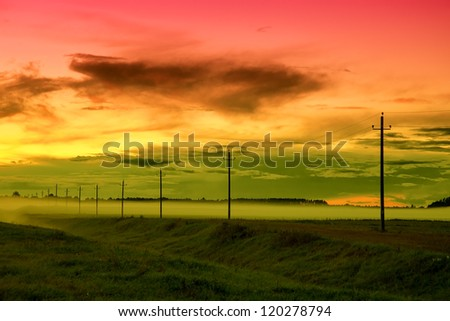 Electricity pylons and lines at dusk over the highway in fog