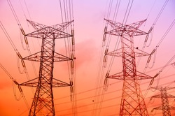 Electricity pylons and lines at sunset