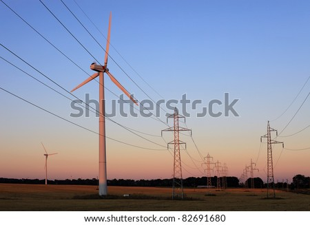 Electricity pylons and wind turbines against sky at sunset