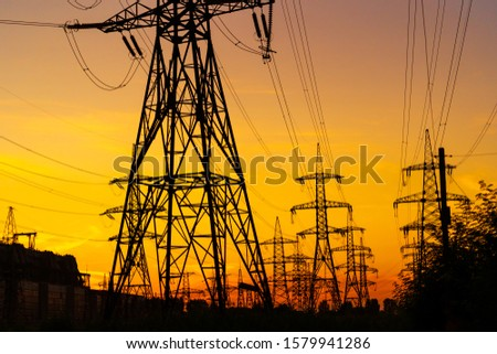 Electricity pylons bearing the power supply across a rural landscape during sunset. Selective focus. #1579941286
