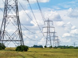 Electricity pylons going into the distance over summertime countryside