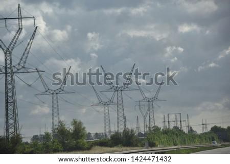 Electricity pylons in a row along a motorway in Denmark #1424471432