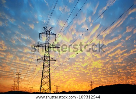 Electricity pylons, power lines and trees silhouetted against a cloudy sky at sunset.