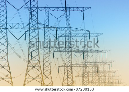 Electricity pylons standing in a row just before sunset