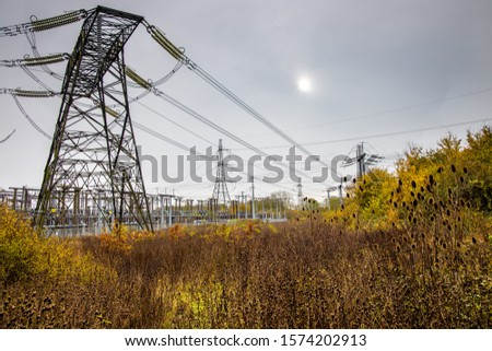 Electricity transformer station in the countryside.  Pylons and plants with autumn hues under a steely grey sky. #1574202913