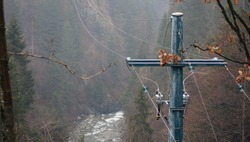 Electricity transmission pole in mountainous areas, electricity transmission over a mountain river