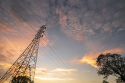 Electricity transmission power lines (High voltage tower) high-voltage lines. Transmission of electricity by means of supports through agricultural areas sunny day with landscape and sunset
