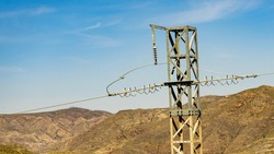 Electricity transmission pylon, power line voltage tower in mountains against blue sky.