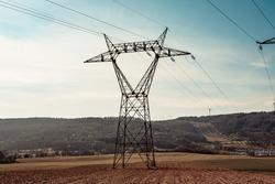 Electricity transmission pylon, power line voltage tower post in spring agricultural landscape.